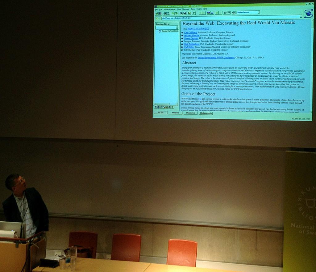 Peter Ström redogör för webbtypografins utveckling. Projektorn visar en webbsida från tidigt nittiotal.